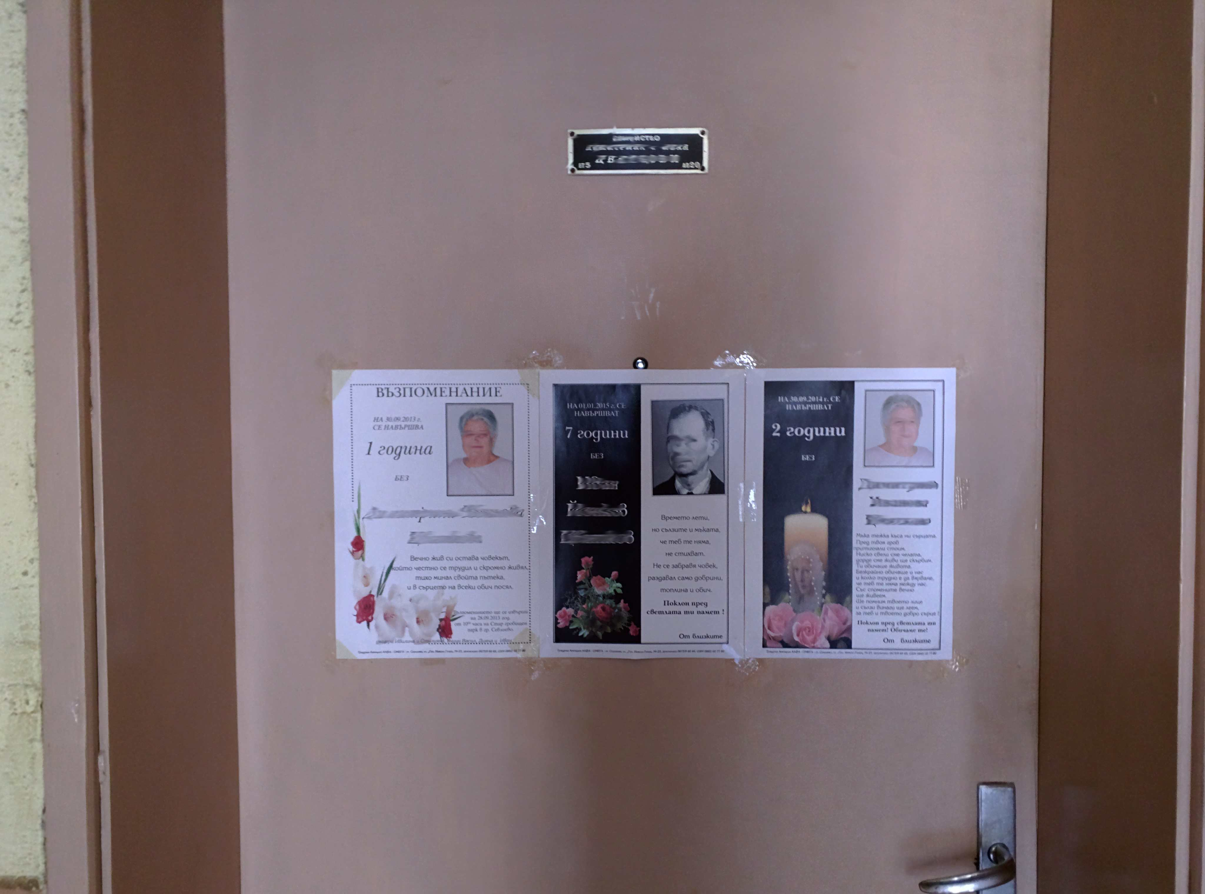 Obituary notices on the front door of a Bulgarian home.