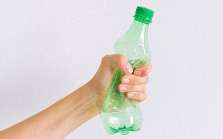 crop unrecognizable woman squashing plastic bottle